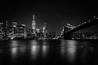 The Manhattan skyline and Brooklyn Bridge at night seen from Bro