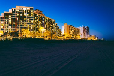 Tire tracks on the beach and hotels at night, in Daytona Beach,