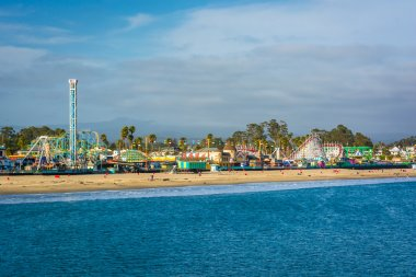 View of the rides on the Santa Cruz Boardwalk and the beach from