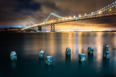 Pier pilings and the San Francisco - Oakland Bay Bridge at night