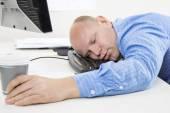 přepracovaní a unavený muž v kanceláři
