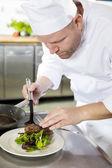 Profesionální kuchař připravit masové jídlo v restauraci