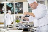 Šéfkuchař přidání Pepřový steak v profesionální kuchyni