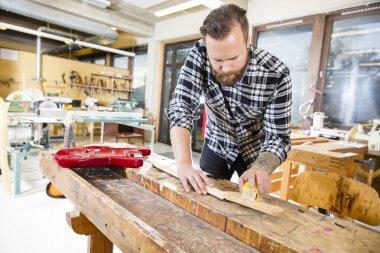 Carpenter sanding a wooden guitar neck in workshop