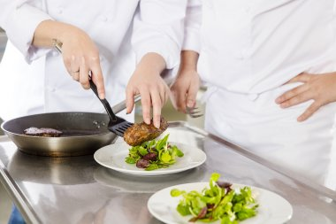 Professional chefs prepares steak dishes at restaurant