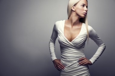 Fashion portrait of a blonde woman in white dress