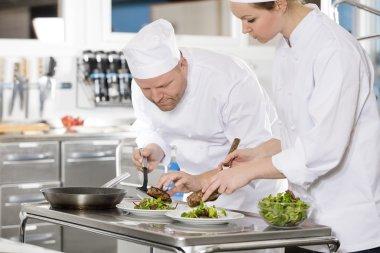 Professional chefs prepare steak dish at restaurant