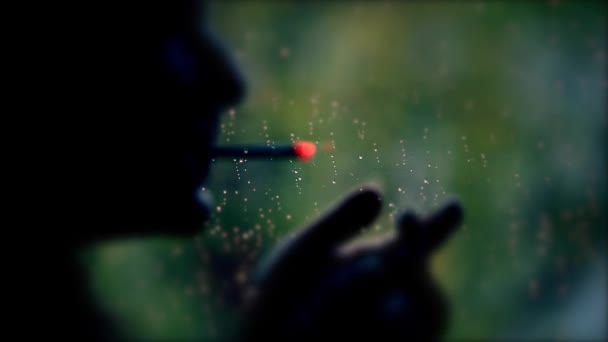 Silhouette of a man  standing by a window and smoking, looking through window on rainy day,rain drops on the window