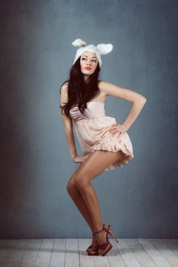 Beautiful sexy woman with long silky hair posing, girl in the image of the rabbit in  pink dress bad bunny sly sexy look play boy for men