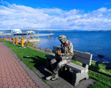 Sidney, BC Canada - November 13, 2020. Sculpture Old Man by the Sea at the fishing pier in Sidney, decorated with red poppies for Remembrance Day celebration