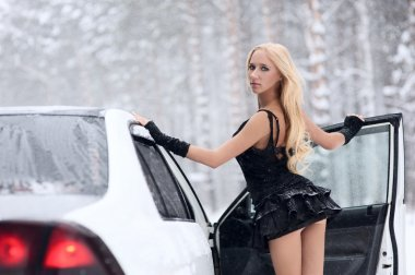 Blonde sits behind the wheel of a white car in the snow