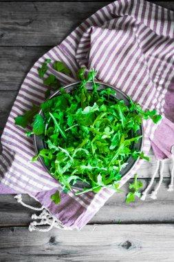 Arugula salad on wooden background