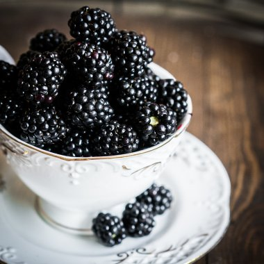 Blackberries in a mug on wooden background