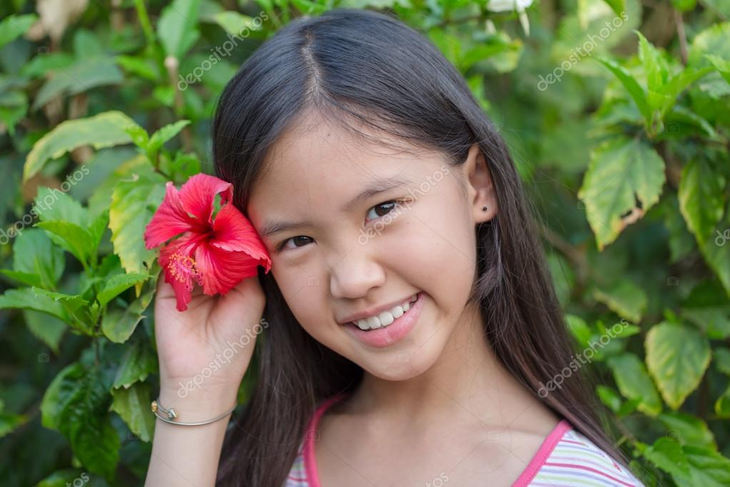 Little Asian Girl Smiling With Chinese Rose In The Garden Stock Photo