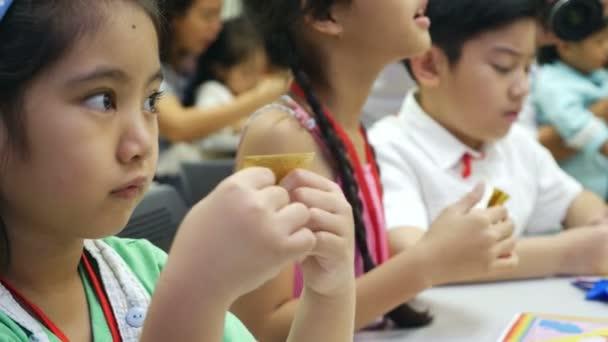 4k: asijské dítě naučit se skládání papíru japonské umění skládání papíru origami, které je často spojen s japonskou kulturou.