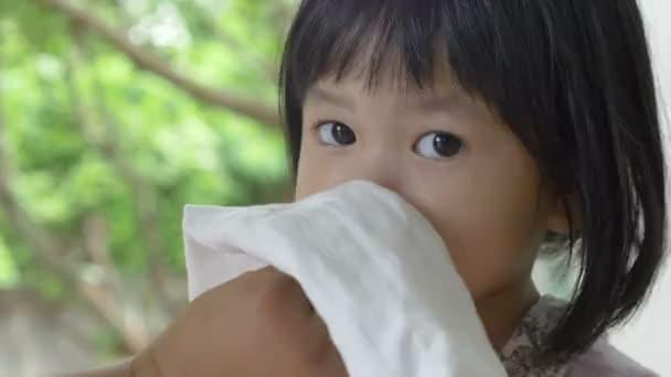 4k: kleine asiatische Kind krank mit Grippe Niesen und sauber von der Mutter