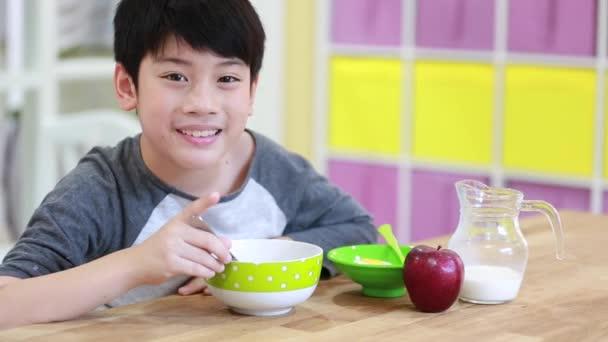 Asijské chlapce jíst cereálie s mlékem s úsměvem tvář
