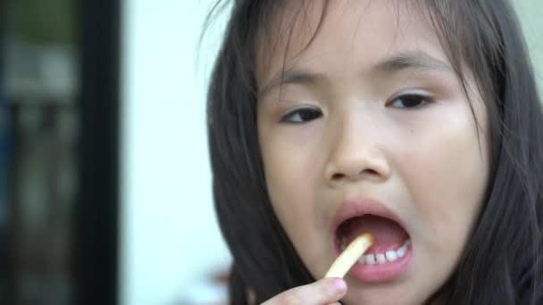 Malá Asijská dívka jí hranolky a pohledu kamery. Slow motion 120 Fps od Sony A6300