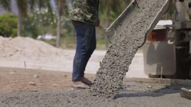 Fließender Beton aus Mischzement-LKW gießt flüssigen Beton in Baustelle.
