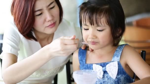 Asian child eating an ice creme with my mother in relax time .