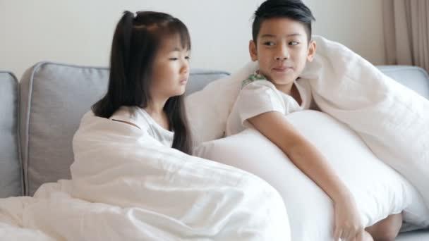 Asijské děti dívat na televizi na pohovce