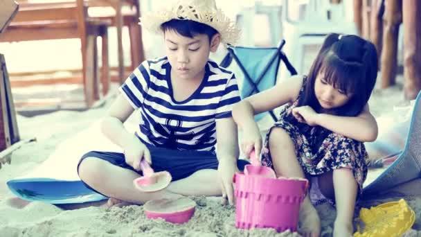 Happy asijské děti hrací písku na pláži