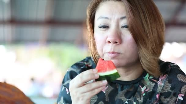 Happy Asian female enjoy eating ripe watermelon .