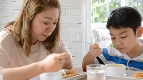 Asian mother with son eating lunch at home