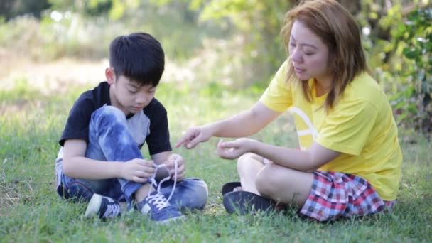 Asian cute child with mother tying laces at the park .
