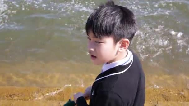 asiatisches Kind gibt Almosen für Fische am Fluss, kämpft um den Futterwurf von Menschen