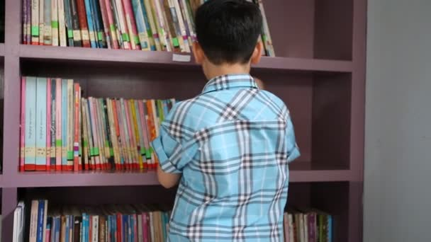 Little Asian student reading book in library .