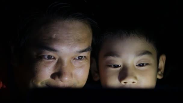 Šťastná rodina otce a syna, při pohledu na notebook na posteli v ložnici