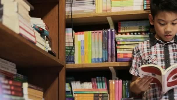 Asijský chlapec čte knihu doma