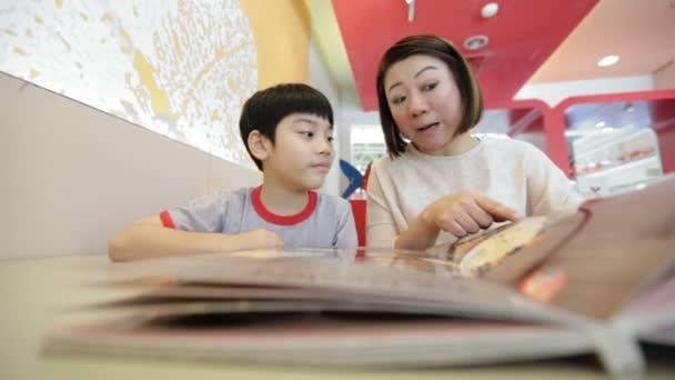 Asijské hezouna s matkou čtení menu knihy a bod. Veselý obličej