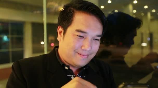 asiatische Geschäftsmann mit dem Handy und trinken Kaffee in der Nacht im Café. schöner Mann wartet auf jemanden, bangkok thailand