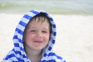 Beautiful baby with blue eyes on the sea background smiling, sweet and gentle. Cute child with atopic dermatitis on the background of the sea