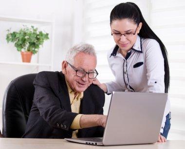 Senior man and young woman looking at laptop