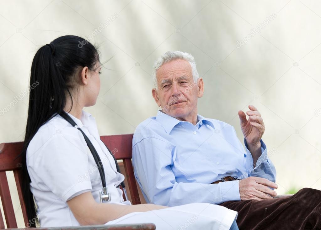 Senior hombre hablando con la joven enfermera en el Banco. Concepto de mayores  cuidados — Foto de budabar