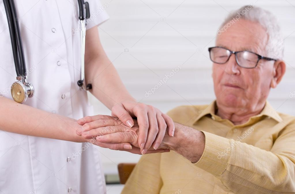 Cerca de las manos de la joven enfermera cogidos de la mano del viejo  hombre. Concepto de mayores cuidados — Foto de budabar