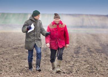 Farmers on plowed field
