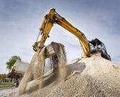 Fotografie Excavator on the gravel pile
