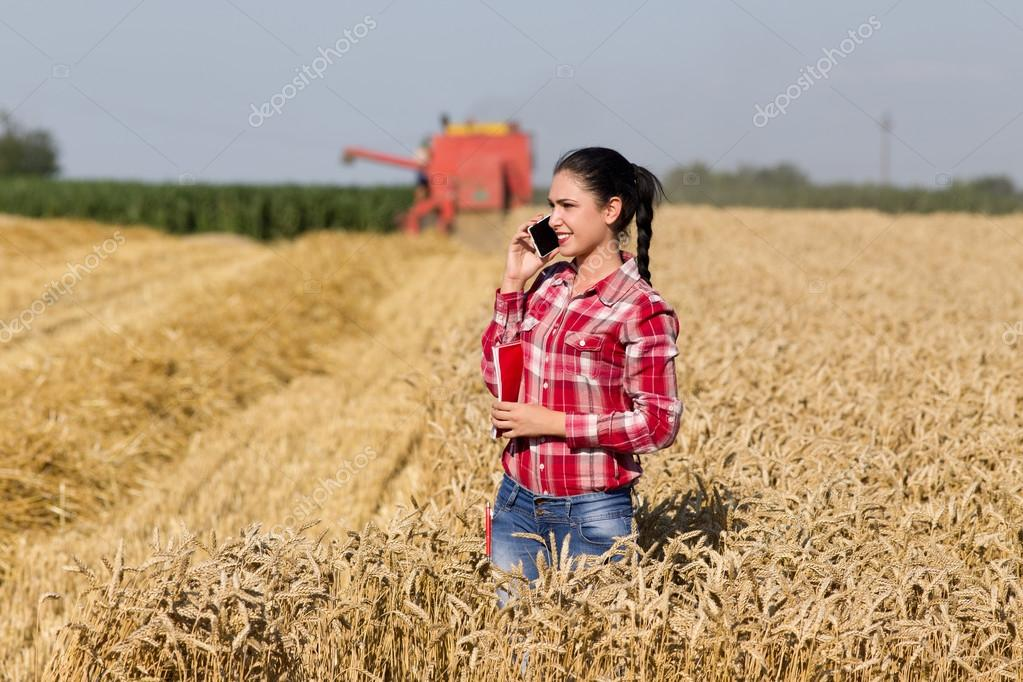 Pretty woman talking on mobile phone in wheat field