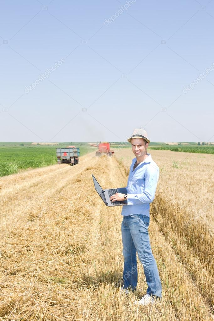 Man with laptop on farmland
