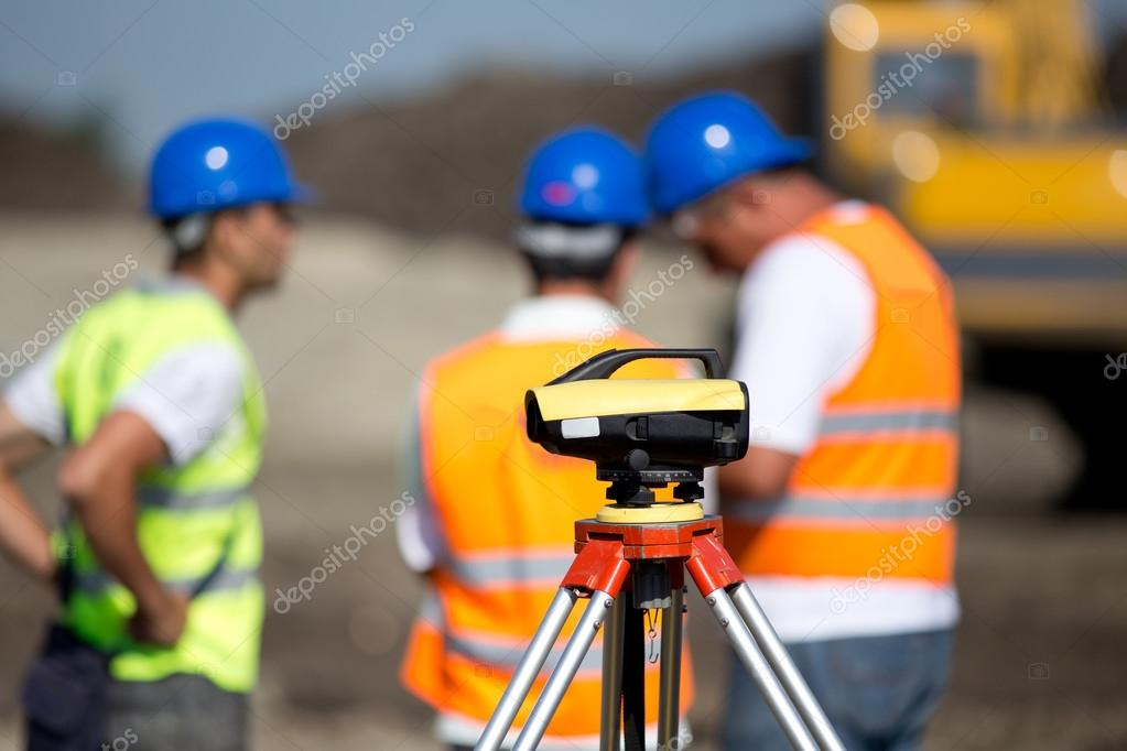 Theodolite and workers at construction site