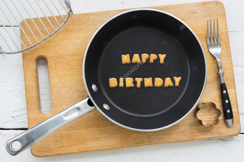 top view of letter collage made of biscuits word happy birthday putting in black frying pan other cooking equipments fork cookie cutter and chopping