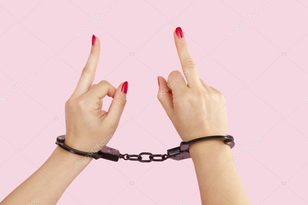 Female hands in handcuffs showing the middle finger. — Stock Photo ...