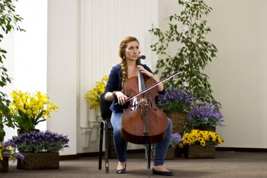 Young girl playing the cello in a large bright hall .Portrates beautiful girl with long hair. Musical Instruments