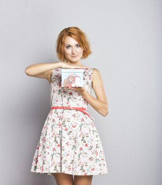 Beautiful red-haired girl with a Christmas present in his hands. Portrait of a slim and beautiful girl on a gray background
