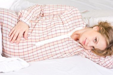 Beautiful pregnant blonde basking in the white bed. Portrait of a pregnant woman at home