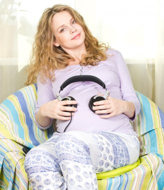Young pregnant woman listening to music on headphones at home closed. Portrait of pregnant woman